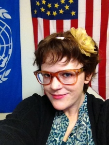 {photo: a woman with an orange, casual pair of glasses and a flower in her hair in front of the Union Cavalry and the UN flags}