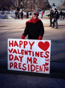 "{photo: a woman wearing a red scarf and red gloves holds a large sign written in red on a white board with a red heart,  which says, ""Happy Valentine's Day Mr. President, We <3 You""}"