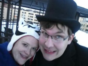 {photo: a selfie of a woman in a badger hat leaning on a man in a top hat, both smiling at the camera}