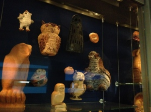 {photo: an exhibition case with several artifacts depicting owls}