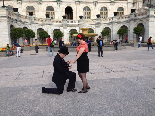 {Photo: a man in a suit and top hat, down on one knee, placing a ring on a standing woman's hand. Woman is wearing an orange-pink dress with a matching flower in her hair}