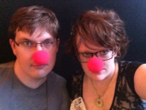 {Photo: a couple poses for a selfie with red clown noses on. One is wearing a pin that says Thunder Thighs}
