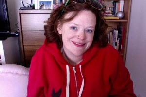 {Photo: the author, a woman with curly hair and a red sweatshirt on symbolizing autism acceptance, in her home)